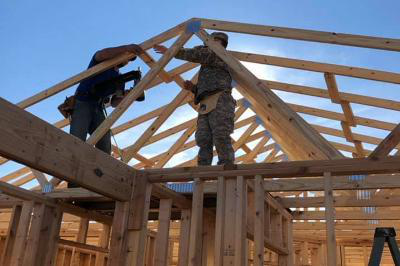 Two cadets nail a roof truss down during a Habitat for Humanity build