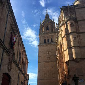 Photo of the Cathedral de Salamanca in Spain, taken by Cadet Emma Pratt on a study abroad trip. The cathedral is show from an angle below the tower, with a clock visible